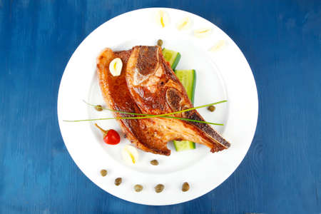 fresh hot roasted lamb meat fillet ready on china plate with tomatoes, green pepper , and garlic on blue wooden table photo