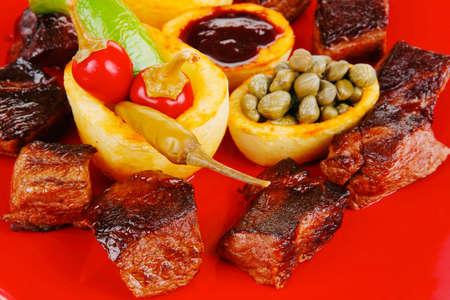 european food: alimentaria europea: la parrilla gulash carne en placa roja con pimientos picantes, alcaparras y aceitunas aceite y salsa de barbacoa