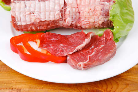 uncooked meat with vegetables on wooden table photo
