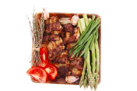 fresh grilled meat beef ribs with asparagus thyme and tomatoes on wooden plate isolated over white background photo