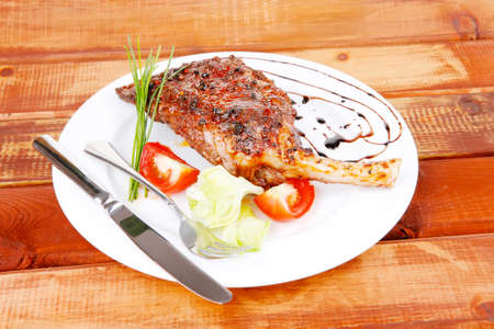 stell: meat over wood: grlled shoulder on plate with tomatoes green lettuce and cutlery on white plate