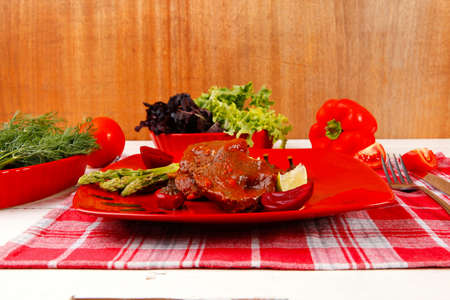 grilled beef pork meat served on red plate with asparagus hot pepper salad and bell on napkin over white wooden table photo
