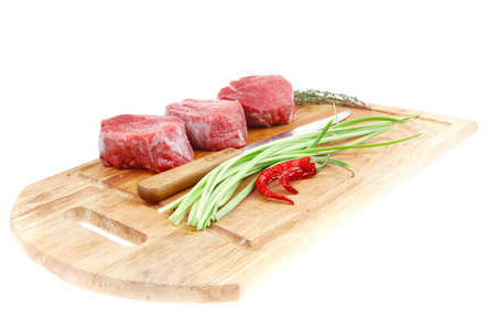 fresh fillet chops : raw beef fillet on wooden board with thyme and red hot dry pepper ready to prepare . isolated over white background photo