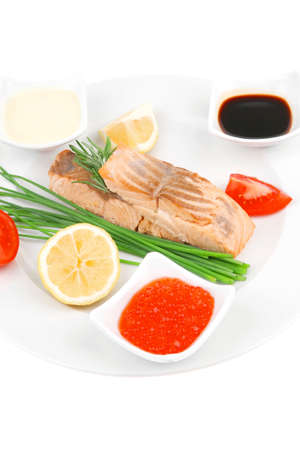 savory sea fish entree : roasted salmon strips with green onion, red caviar , mayonnaise and soybean sauces , and tomatoes on white dish isolated over white background photo