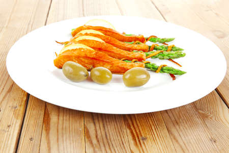 roasted salmon slices with asparagus lemon fried orange peel green olives and cutlery on white plate over wooden table photo