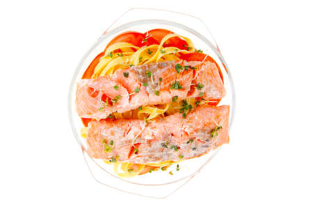 fresh fried natural pink salmon on italian traditional tagliatelles backed with tomato and vegetables isolated over white background photo