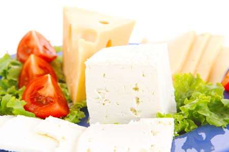 set of gourmet delicatessen cheese slice and chunk white goat greek yellow french aged on green lettuce salad with tomatoes on blue plate isolated over white  photo