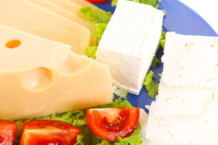 set of gourment delicatessen cheese slice and chunk  white goat greek yellow french aged on green lettuce salad with tomatoes on blue plate isolated over white  photo