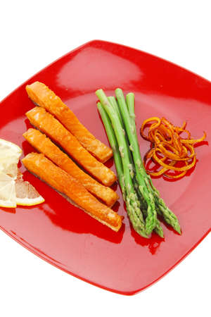 grilled salmon slices with asparagus lemon and fried orange peel on red plate isolated over white  photo