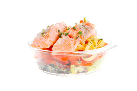 fresh fried natural pink salmon on italian traditional tagliatelles backed with tomato and vegetables isolated over white  photo
