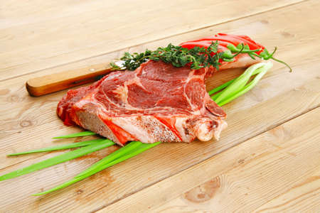 boned: raw meat : boned fresh lamb ribs served with thyme , red chili pepper , and green onion on wooden board