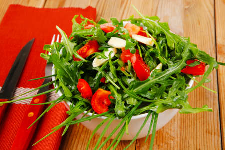 vegetable food : green salad with raw tomato and garlic in white bowl over wood served with cutlery photo