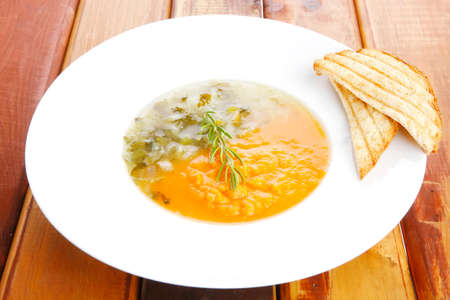 vegetable soup: european cuisine: dual components vegetable soup with toasts over wood