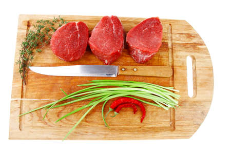 raw meat : fresh beef fillet with thyme and red hot dry pepper on wooden plate . isolated over white background photo