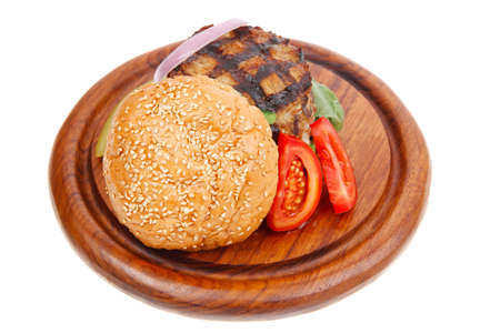 extra thick hot beef meat hamburger dinner on wooden plate with tomatoes and salad isolated on white background photo