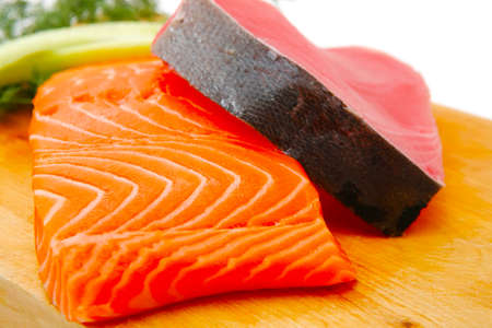 tuna fillet: fresh raw salmon and red tuna fish pieces over wooden board isolated on white background