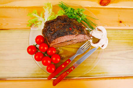 beef slice on transparent plate and vegetables on wood photo