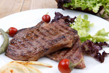 ready to cook food: meat food : roast steak boneless with roast onion and red hot peppers, served on green lettuce salad on dish isolated over wooden table