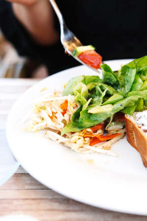 vegetable salad on fried eggs with bread om white plate outside cafe photo