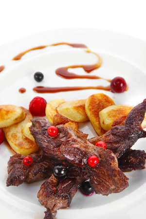 grilled beef meat with berries fried potatoes and cherry under sweet honey sauce on white plate isolated over white  photo