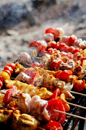 chicken shish kebab on bbq grill in sauce on skewers with tomatoes and peppers photo