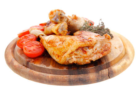 chicken meat: grilled chicken drumstick with tomatoes and thyme on wooden plate isolated over white background