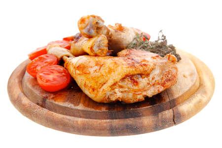 carne de pollo: Muslo de pollo a la parrilla con tomate y tomillo en un plato de madera aislada sobre fondo blanco