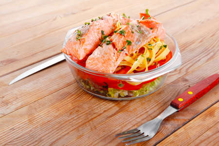 fresh fried natural pink salmon on italian traditional tagliatelles backed with tomato and vegetables served over wooden table with cutlery photo