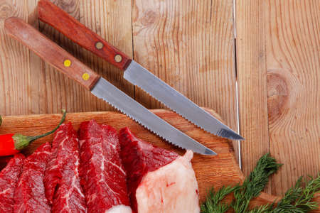 fresh raw beef meat steaks on wooden cut board over wooden table with dill and stainless steel knife photo