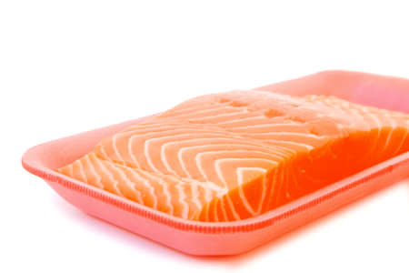 piece of fresh raw salmon on red tray isolated on white background . shallow dof photo