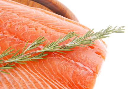raw salmon fillet isolated on wooden plate with rosemary photo