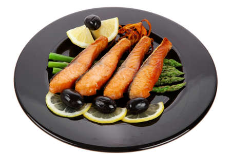 grilled salmon slices with asparagus lemon and olives on black plate isolated over white background photo