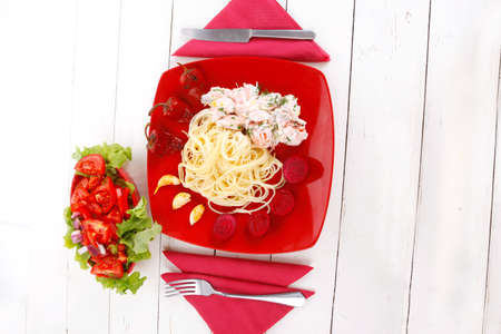mediterranean cuisine: fresh rose wild salmon baked in cream cheese sauce with italian pasta and red hot pepper on plate over white wooden table with vegetable salad photo