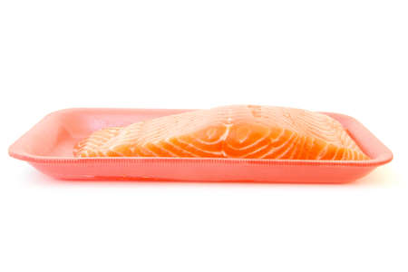 piece of fresh raw salmon on red tray isolated on white background photo