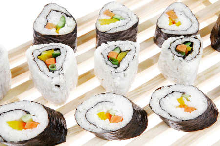 Maki Roll with Deep Fried Vegetables inside . on wooden grid . isolated over white . Japanese Cuisine photo