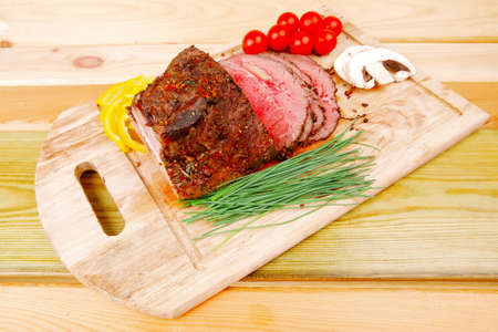 beef barbecue served on big wooden plate photo