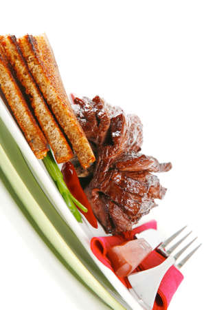 served cutted meat with bread and dishware photo
