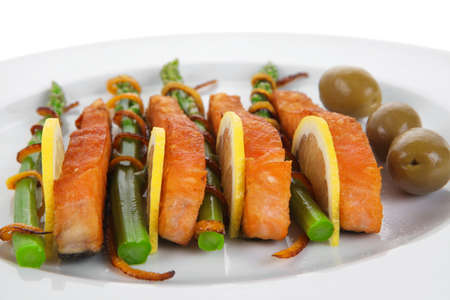 grilled salmon slices with asparagus lemon green olives and fried orange peel on big plate isolated over white background photo