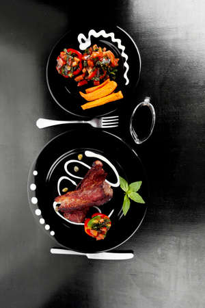 fresh red beef meat steak barbecue garnished vegetable salad sweet potato and basil on black plate over black wooden table with bbq sauce in sauceboat photo