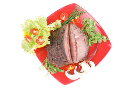 beef on red plate with vegetables over white photo