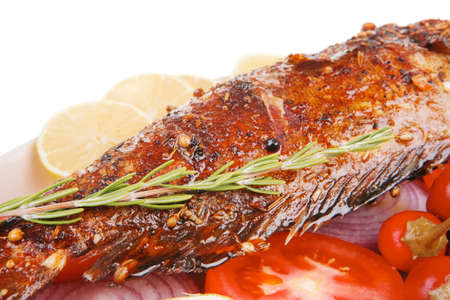 sunfish: savory: whole fryed sunfish over plate with tomatoes lemons and peppers . shallow dof Stock Photo