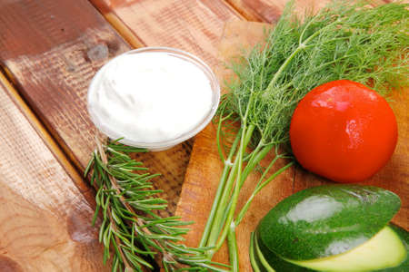vegetables and sour cream on wooden table photo