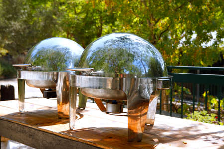 stainless: two closed stainless steel cloche on wooden table on restoran outside party