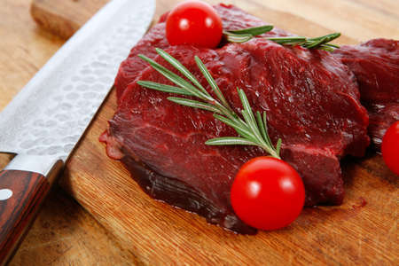 fresh raw beef steak with cherry tomatoes rosemary twig on wood cut plate over table with japanese layered stainless steel knife photo