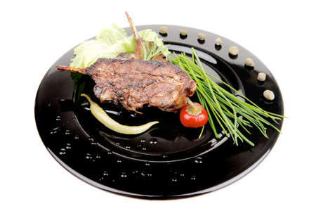 served main dish : lamb meat ribs on plate with hot peppers and capers on black plate isolated over white background photo