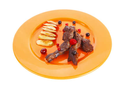 grilled beef meat with berries fried potatoes and cherry under sweet honey sauce on orange plate isolated over white background photo