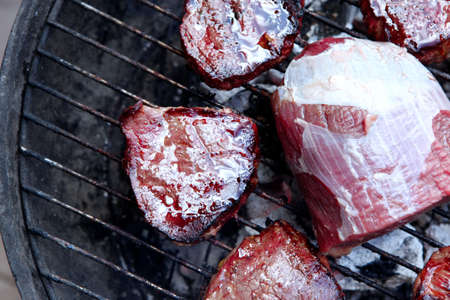 butch: fresh raw big beef fillet chunk with roast slices on charcoal bbq grill