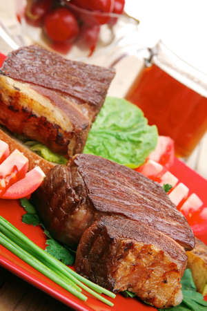 meat savory : beef fillet mignon grilled and garnished with vegetables , juice and olives on red plate over wooden table photo