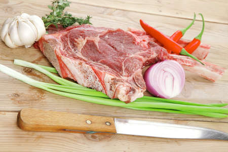 boned: raw meat : boned fresh lamb ribs served with thyme , garlic and red chili pepper on wooden board Stock Photo