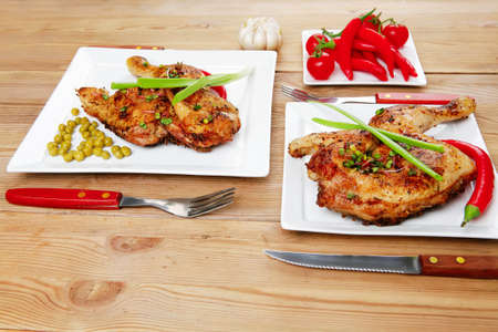 quarters: meat : chicken quarters garnished with green sweet peas and and cutlery on white plates over wooden table Stock Photo